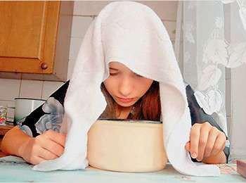 Девочка дышит над кастрюлей под полотенцем