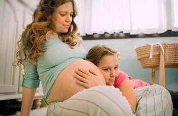 Девочка слушает живот беремнной мамы