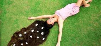 Девушка с длинным волосом лежит на траве