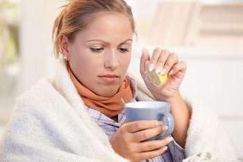 Девушка выдавливает сок лимона в кружку