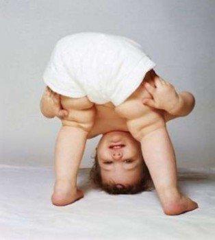 Малыш стоит на ногах и голове
